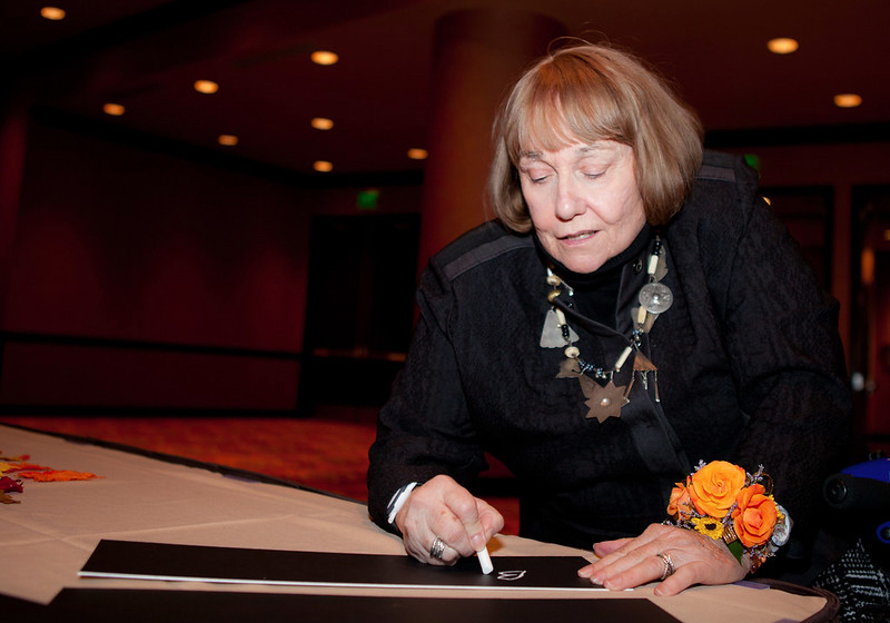 Betty Quadracci signs a signature plaque at the Milwaukee Press Club's Hall of Fame dinner in 2012.