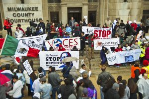Members of Voces de la Frontera and other area activist organizations stand on the steps of the Milwaukee County Courthouse during a 2014 protest.