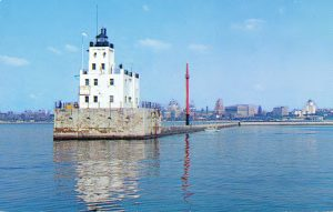 "This postcard illustrates Milwaukee's downtown and breakwater light on Lake Michigan, captioned as ""The Gateway to the World."""