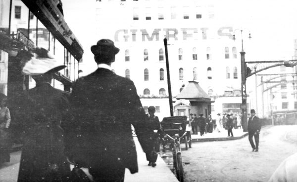 Two people walk west on Wisconsin Avenue in the early twentieth century towards the Gimbel's Department Store.  Their dress suggests their gender identity as a woman [left] and a man [right].