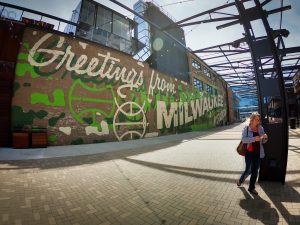 "This ""Greetings from Milwaukee"" mural welcomes visitors to the growing district around the Fiserv Forum."
