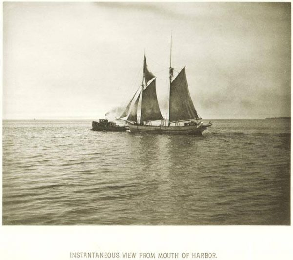 A tugboat pulls a sailing ship out of the Milwaukee Harbor toward Lake Michigan in 1885.